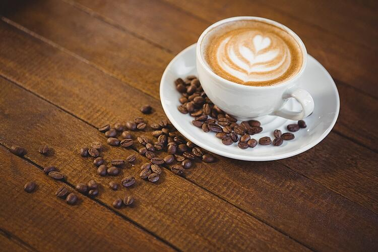Cup of cappuccino with coffee art and coffee beans on wooden table