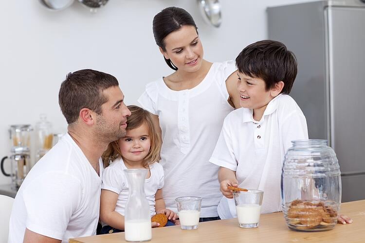 Parents and children  drinking milk in the kitchen