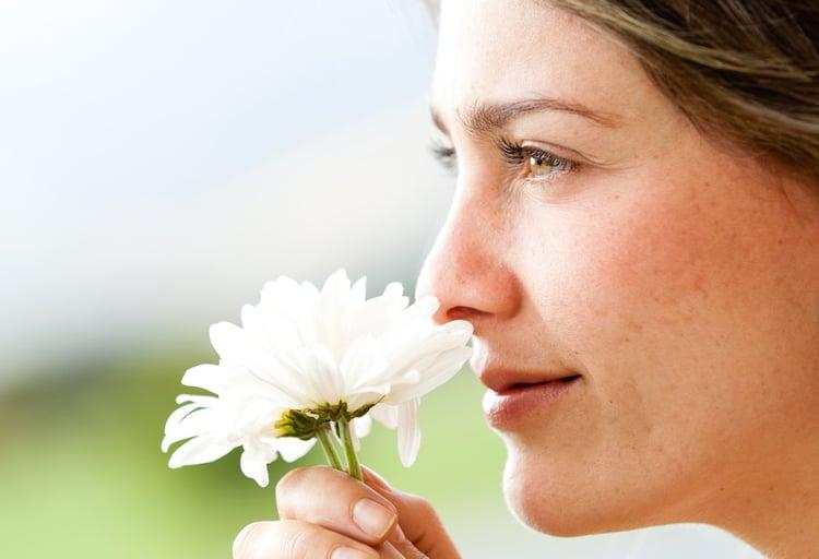 Portrait of a beautiful woman smelling a flower